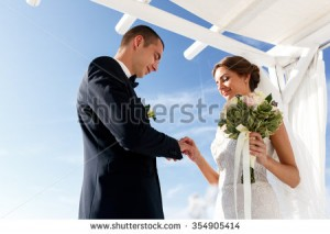 stock-photo-happy-groom-and-bride-exchanging-rings-at-aisle-during-ceremony-sea-and-mountains-354905414