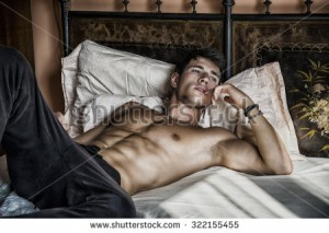 stock-photo-shirtless-sexy-male-model-lying-alone-on-his-bed-in-his-bedroom-looking-away-with-a-seductive-322155455